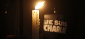"A person holds a candle in front a placard which reads ""I am Charlie"" to pay tribute during a gathering at the Place de la Republique in Paris"